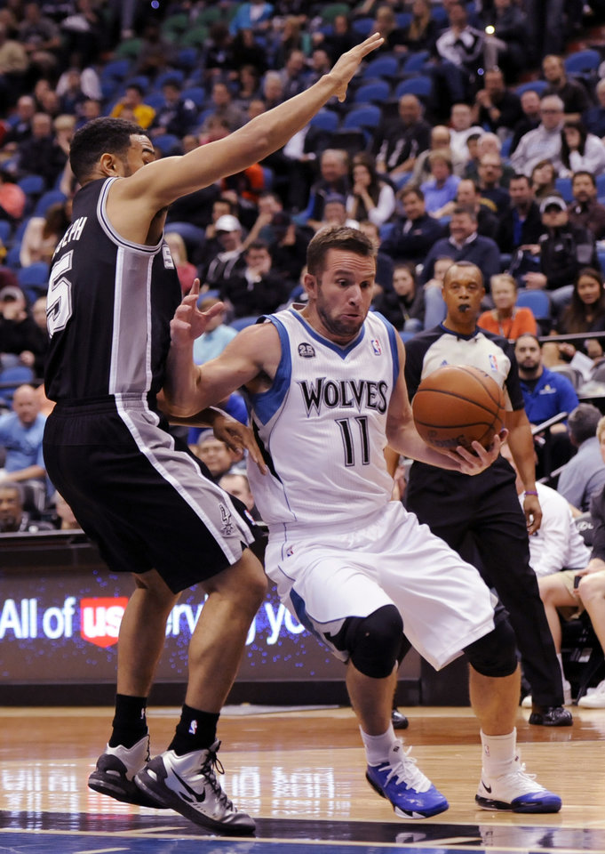 Photo - Minnesota Timberwolves' J.J. Barea (11) drives against San Antonio Spurs' Cory Joseph (5) in an NBA basketball game at the Target Center on in Minneapolis on Tuesday, April 8, 2014. Timberwolves won 110-91. (AP Photo/Hannah Foslien)