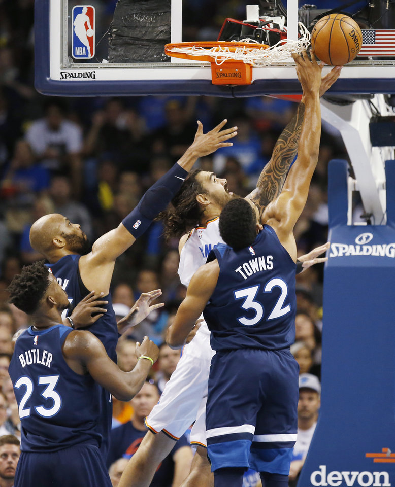 Photo - Oklahoma City's Steven Adams (12) tries to score as Minnesota's Karl-Anthony Towns (32), Taj Gibson (67) and Jimmy Butler (23) defend during an NBA basketball game between the Oklahoma City Thunder and the Minnesota Timberwolves at Chesapeake Energy Arena in Oklahoma City, Sunday, Oct. 22, 2017. Minnesota won 115-113. Photo by Nate Billings, The Oklahoman