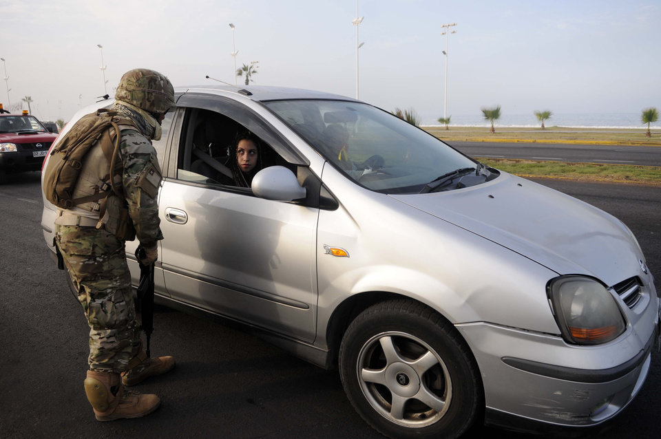 Photo - A Chilean soldier inspects a car in the northern town of Iquique, Chile, after magnitude 8.2 earthqauke struck the northen coast of Chile, Wednesday, April 2, 2014. Chilean President Michelle Bachelet flew to the region to review damage in daylight after declaring a state of emergency and sending a military plane with 100 anti-riot police to join 300 soldiers who were deployed to prevent looting and round up escaped prisoners. (AP Photo/Cristian Viveros) NO PUBLICAR EN CHILE