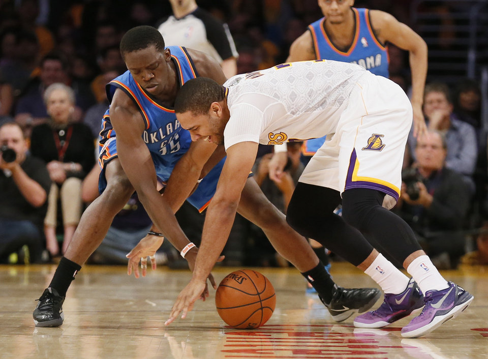 Photo - Oklahoma City Thunder point guard Reggie Jackson, left, and Los Angeles Lakers small forward Xavier Henry reach for a loose ball during the first half of an NBA basketball game in Los Angeles, Sunday, March 9, 2014. (AP Photo/Danny Moloshok)