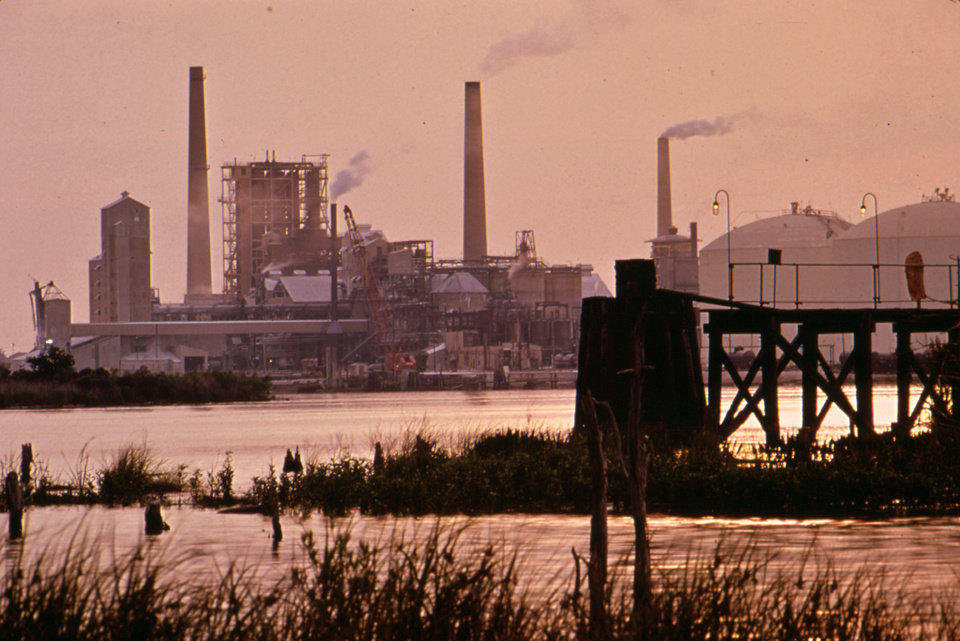 "This June 1972 photo released by the U.S. National Archives shows a sunrise over the Olin-Mathieson Plant on the Calcasieu River in Calcasieu Parish, La. The photo was taken for the ""Documerica"" program, 1972-1977, instituted by the then new Environmental Protection Agency to document subjects of environmental concern. (AP Photo/U.S. National Archives, Marc St. Gil)"