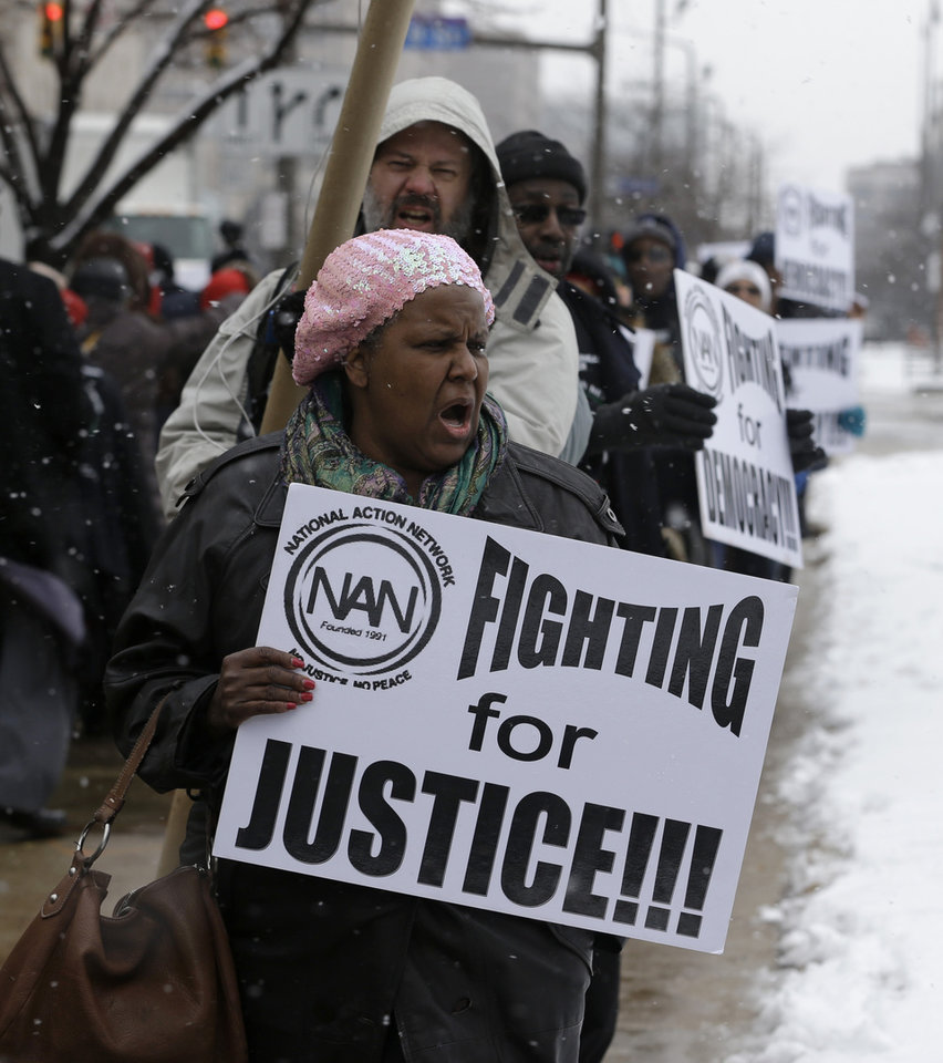 Photo - Jackie Turnboe, from Detroit Mich., protests outside the offices of JonesDay Monday, March 25, 2013, in Cleveland. Detroit's new emergency manager, Kevyn Orr, said Monday he would offer a