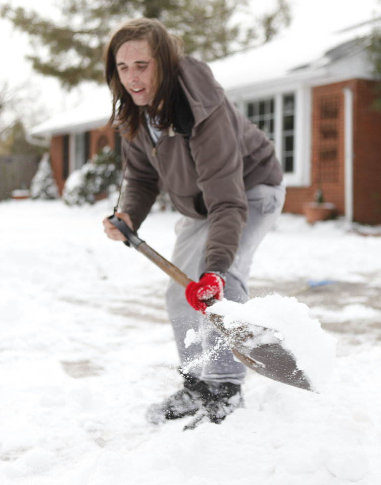 Photo - Chaz Stokes clears snow from driveways in Oklahoma City, OK, Thursday, Feb. 3, 2011. By Paul Hellstern, The Oklahoman
