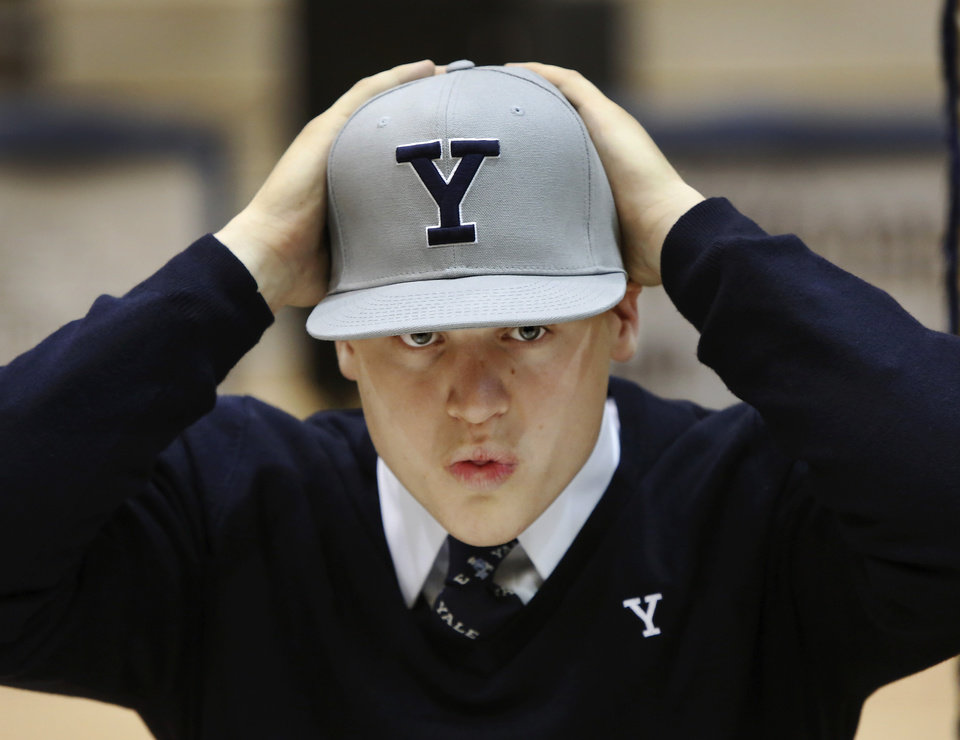 Jackson Stallings adjusts his Yale University hat at the end of the signing ceremony. More than a dozen Southmoore High School athletes signed letters of intent to play at various colleges and universities during an afternoon signing ceremony in the school\'s gymnasium on Wednesday, Feb. 6, 2013. Photo by Jim Beckel, The Oklahoman
