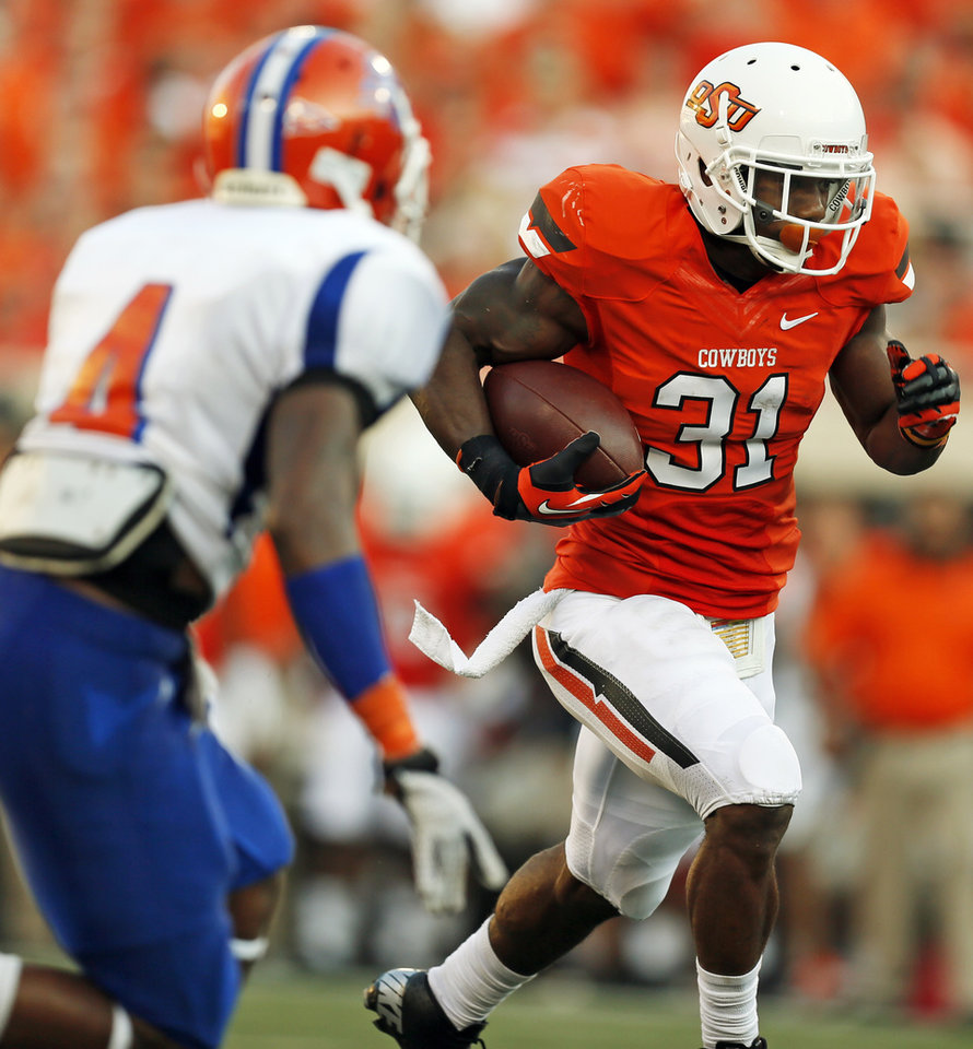 Photo - OSU's Jeremy Smith carries the ball against Savannah State's John Wilson (4) during a college football game between Oklahoma State University (OSU) and Savannah State University at Boone Pickens Stadium in Stillwater, Okla., Saturday, Sept. 1, 2012. Photo by Nate Billings, The Oklahoman