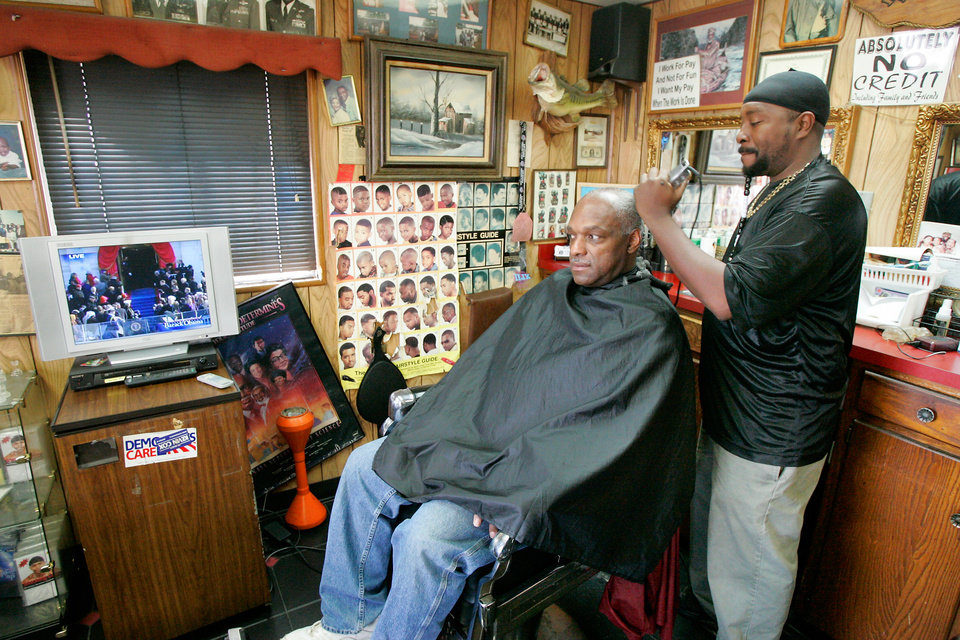 Photo - Philip Dunlap watches the Inauguration of President Barack Obama while Phillip Gates cuts his hair at Gates Barber Shop at NE 26th and Martin Luther King Blvd. in Oklahoma City. January  20, 2009.  BY STEVE GOOCH, THE  OKLAHOMAN.