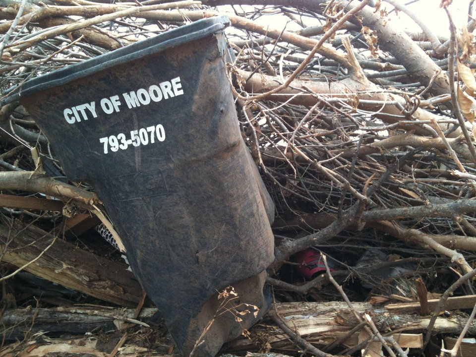 Photo - A City of Moore trash bin sits among broken trees and rubble in Moore. PHOTO BY ADAM SHELTON