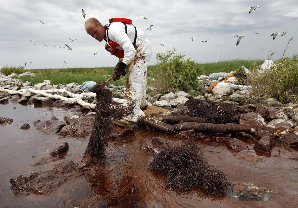 Photo - FILE- In this June 4, 2010 file photo, a worker picks up blobs of oil with absorbent snare on Queen Bess Island at the mouth of Barataria Bay near the Gulf of Mexico in Plaquemines Parish, La. U.S. District Judge Carl Barbier ruled Thursday, Sept. 4, 2014, in New Orleans, La., that BP acted recklessly and bears most of the responsibility for the oil spill. The ruling exposes BP to about $18 million in civil fines under the Clean Water Act.  (AP Photo/Gerald Herbert, File)