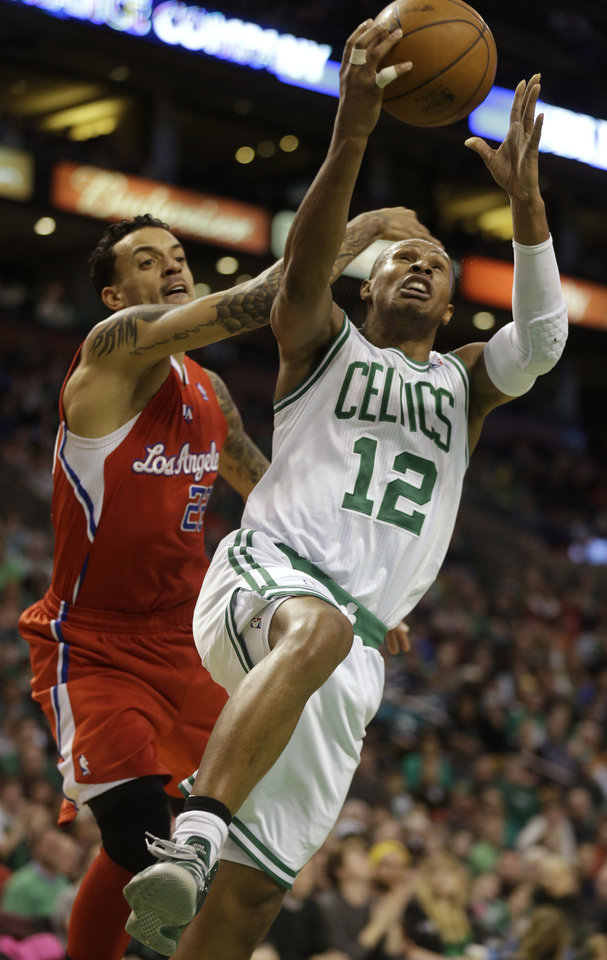 Boston Celtics guard Leandro Barbosa (12), right, drives toward the basket under pressure from Los Angeles Clippers forward Matt Barnes, left, in the fourth quarter of an NBA basketball game at the TD Garden in Boston, Sunday, Feb. 3, 2013. The Celtics defeated the Clippers 106-104. (AP Photo/Steven Senne)