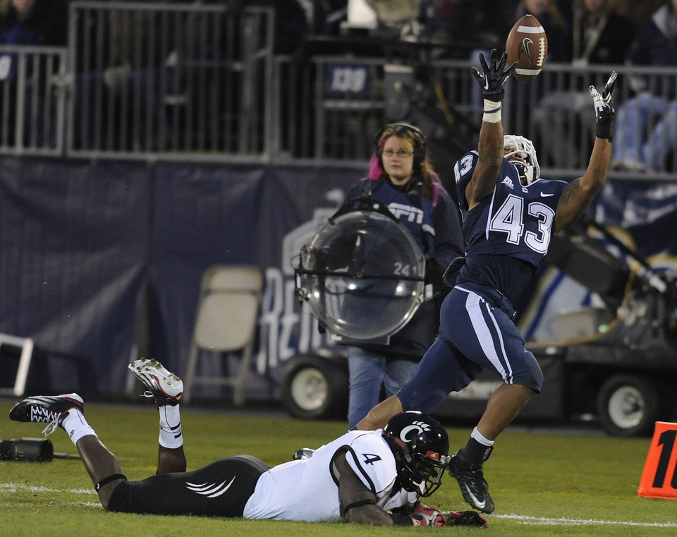 Photo - Connecticut running back Lyle McCombs (43) reaches for a pass while defended by Cincinnati linebacker Maalik Bomar (4) during the first half of an NCAA college football game at Rentschler Field in East Hartford, Conn., Saturday, Dec. 1, 2012.  The pass was incomplete. (AP Photo/Jessica Hill)