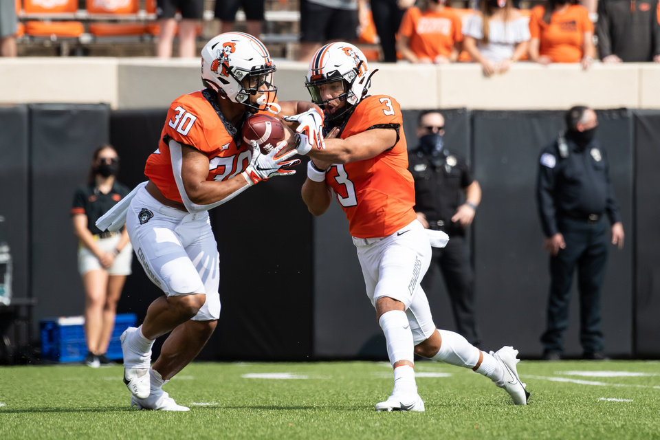 Photo - Oklahoma State quarterback Spencer Sanders (3) hands off to running back Chuba Hubbard. [Rob Ferguson/USA Today Sports[
