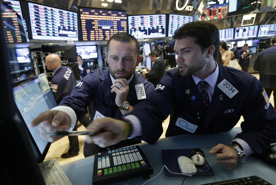 Photo - Specialists Christopher Gildea, left, and Joseph Dreyer, confer at their posts on the floor of the New York Stock Exchange Monday, July 22, 2013. The stock market is opening mixed after McDonald's reported poor quarterly earnings. (AP Photo/Richard Drew)