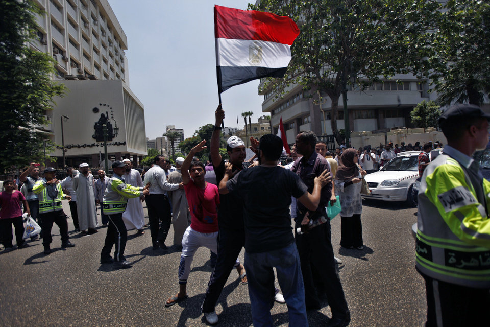 Photo -   Pro and anti-Morsi protesters gather in front of the parliament building in Cairo, Egypt, Tuesday, July 10, 2012. Egypt's Islamist-dominated parliament convened Tuesday in defiance of a ruling by the country's highest court and swiftly voted to seek a legal opinion on the decision that invalidated the chamber over apparent election irregularities. (AP Photo/Khalil Hamra)
