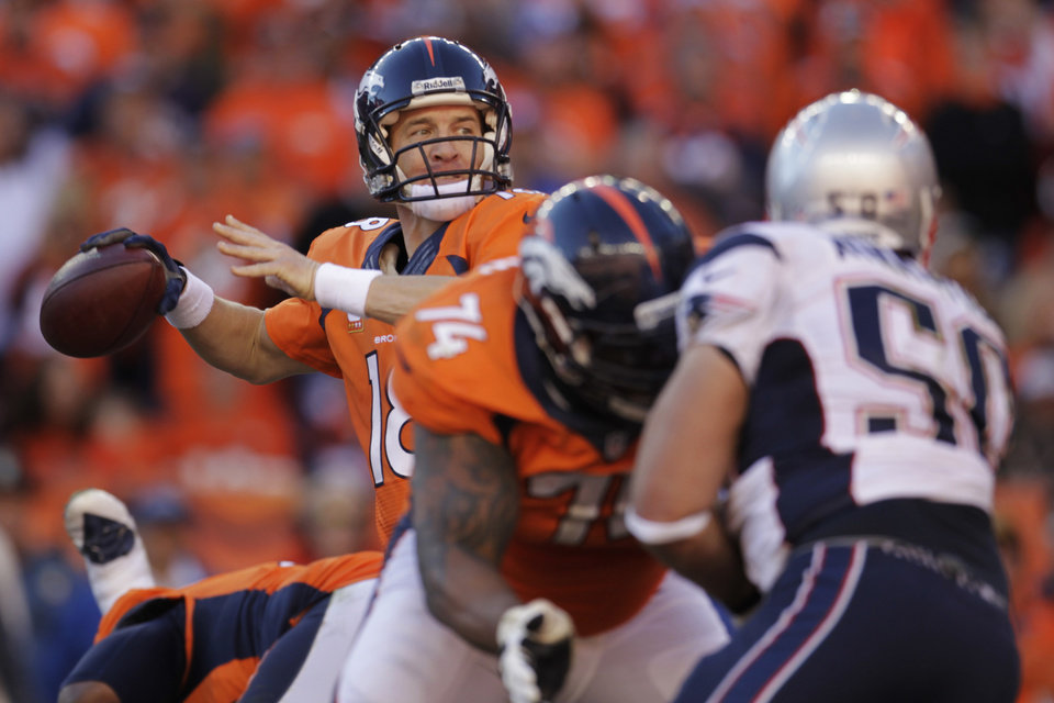 Photo - Denver Broncos quarterback Peyton Manning (18) passes during the second half of the AFC Championship NFL playoff football game against the New England Patriots in Denver, Sunday, Jan. 19, 2014. (AP Photo/Joe Mahoney)