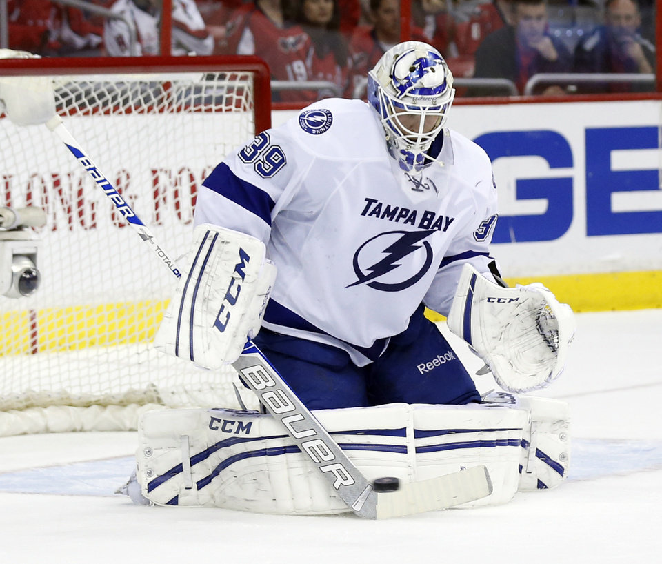 Photo - Tampa Bay Lightning goalie Anders Lindback (39), from Sweden, deflects a shot in the first period of an NHL hockey game against the Washington Capitals, Sunday, April 13, 2014, in Washington. (AP Photo/Alex Brandon)