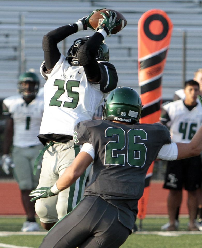 Photo - Edmond Santa Fe's Darran Williams catches a pass in front of Norman North player Paxton Pennington during a high school football scrimmage at Harve Collins Field in Norman, Okla., on Thursday, Aug. 21, 2014. Photo by Steve Sisney, The Oklahoman