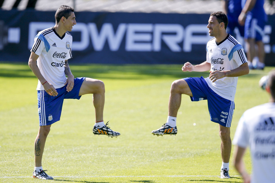 Photo - Argentina's Angel di Maria, left, talks to teammate Maxi Rodriguez as they warm up during a training session in Vespasiano, near Belo Horizonte, Brazil, Friday, June, 13, 2014. Argentina will play in group F of the Brazil 2014 soccer World Cup. (AP Photo/Victor R. Caivano)