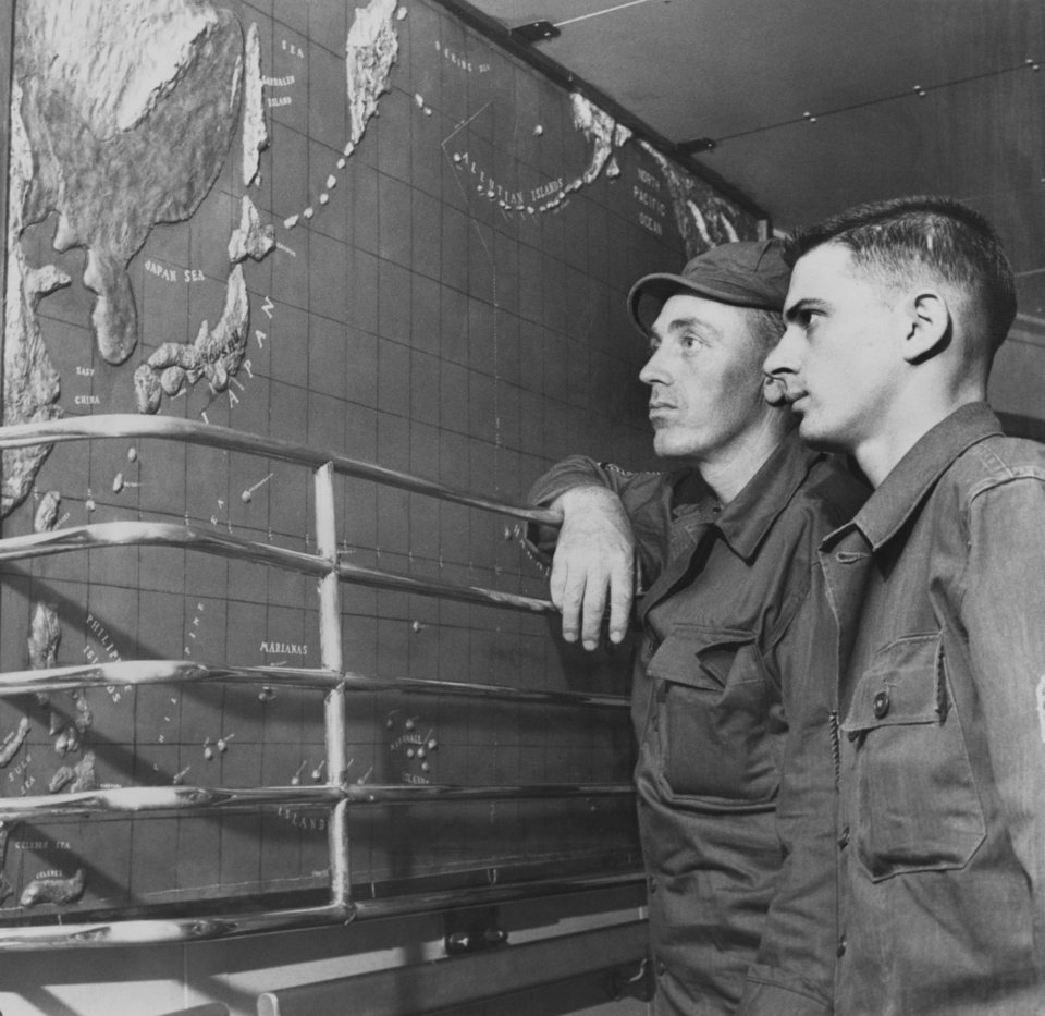 Photo - Giant Map Helps Thunderbirds Check Ship's Position.  The giant relief map of the Pacific ocean in the promenade deck lobby is an item of great interest for Thunderbirds on their way to Japan.  It makes checking the ship's position a cinch.  Looking it over are M/Sgt. George D. Guinn, Tryon, Okla., left, and Sgt. Linnet Wetwiska, 18 1/2 NW 14.  Guinn is a member of the 700th ordinance company and Wewiska works in the training section of division headquarters. Photo by Ron Pyer of 45th Division Photo.  Dated 04/07/1951.  Published in The Oklahoma City Times 04/11/1951.