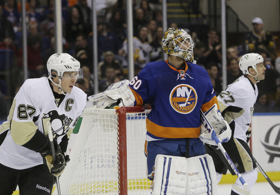 Photo - Pittsburgh Penguins' Sidney Crosby (87) and teammate Craig Adams (27) skate past New York Islanders goalie Kevin Poulin (60) after Crosby scored during the first period of an NHL hockey game, Thursday, Jan. 23, 2014 in Uniondale, N.Y. (AP Photo/Frank Franklin II)