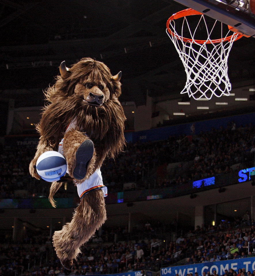 Oklahoma City mascot Rumble the Bison dunks the ball during a break in the action at the NBA basketball game between the Oklahoma City Thunder and the Dallas Mavericks at Chesapeake Energy Arena in Oklahoma City, Monday, March 5, 2012. The Thunder won, 95-91. Photo by Nate Billings, The Oklahoman