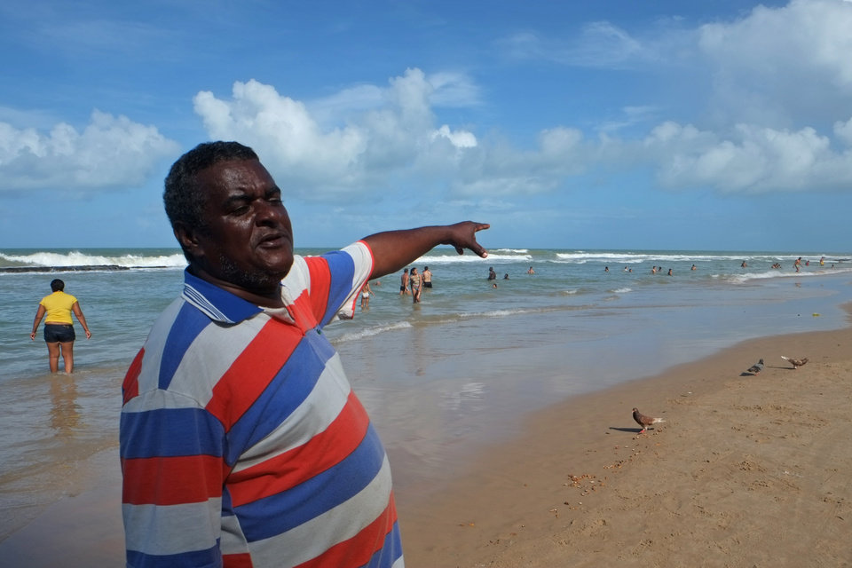 Photo - In this  June 15, 2014, photo, David Jose de Lima, who rents chairs and umbrellas at Boa Viagem beach, points to a spot where an 18-year-old Sao Paulo woman was killed in a shark attack in July 2013, in Recife, Brazil. De Lima considers it part of his job to tell everyone new to the beach about the dangers and always issues a warning for swimmers not to cross the reef into open water. (AP Photo/Lawrence Rincon)