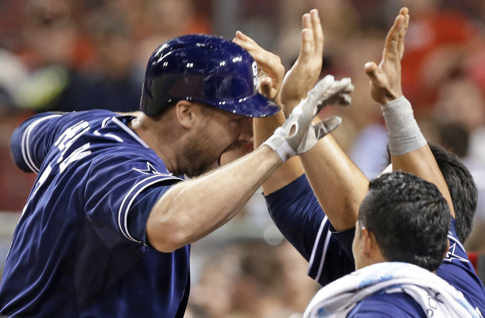 Photo - San Diego Padres' Chase Headley, left, is congratulated after hitting a solo home run off Cincinnati Reds relief pitcher Aroldis Chapman in the ninth inning of a baseball game, Tuesday, May 13, 2014, in Cincinnati. San Diego won 2-1. (AP Photo)