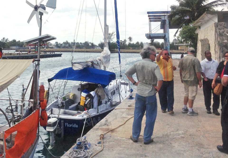 Photo - A state security officer, in yellow, instructs journalists to stop making pictures of Joshua Hakken's blue sailboat, Salty, docked at the Hemingway Marina, in Havana, Cuba, Tuesday, April 9, 2013. Hakken and his wife Sharyn, who had lost custody of their two young boys, allegedly kidnapped them from Sharyn's parents and fled by boat to Havana. A foreign ministry official told The Associated Press in a written statement Tuesday that Cuba had informed U.S. authorities of the country's decision to turn over Hakken, his wife and their two young boys. She did not say when the handover would occur. (AP Photo/Peter Orsi)