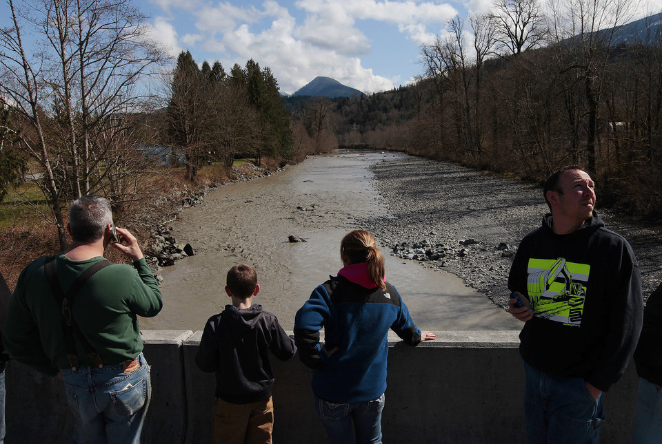 Photo - Residents watch as debris comes down the Stillaguamish River from the Whitman Road bridge east of Oso Sunday, March 23, 2014. (AP Photo /The Herald, Mark Mulligan)