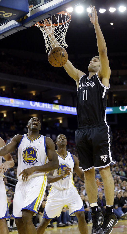 Photo -   Brooklyn Nets' Brook Lopez (11) follows through on a shot next to Golden State Warriors' Festus Ezeli (31) during the first half of an NBA basketball game in Oakland, Calif., Wednesday, Nov. 21, 2012. (AP Photo/Marcio Jose Sanchez)