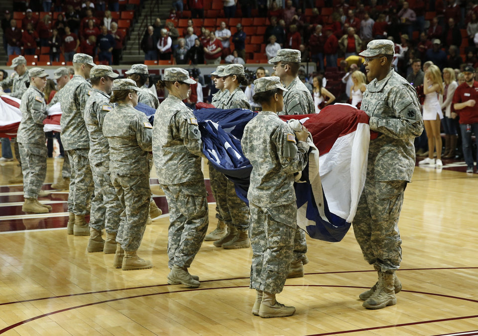 Photo - Members of the military hold an American Flag during the opening ceremonies as the University of Oklahoma Sooners (OU) men play the Iowa State Cyclones (ISU) in NCAA, college basketball at The Lloyd Noble Center on Saturday, Jan. 11, 2014  in Norman, Okla. Photo by Steve Sisney, The Oklahoman