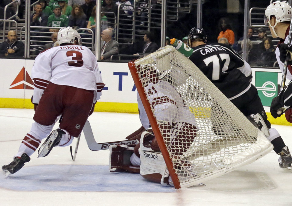 Photo - Los Angeles Kings center Jeff Carter (77) topples into the goal with Phoenix Coyotes goalie Mike Smith (41) and defenseman Keith Yandle 3) in the second period of an NHL hockey game in Los Angeles Monday, March 17, 2014.  (AP Photo/Reed Saxon)