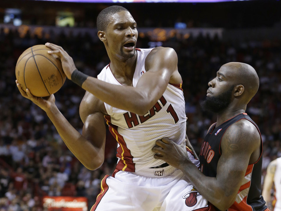 Photo - Miami Heat center Chris Bosh (1) looks for an opening past Toronto Raptors forward Quincy Acy during the first half of an NBA basketball game on Wednesday, Jan. 23, 2013, in Miami. (AP Photo/Wilfredo Lee)