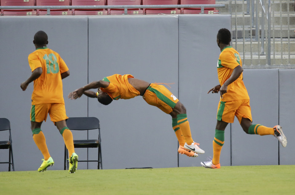 Photo - Zambia's Christopher Katongo, center, does a back flip with teammates Emmanuel Mbola, left, and George Chilufya, right, after scoring a goal against Japan during the first half of an international friendly soccer match in Tampa, Fla., Friday, June 6, 2014. (AP Photo/John Raoux)