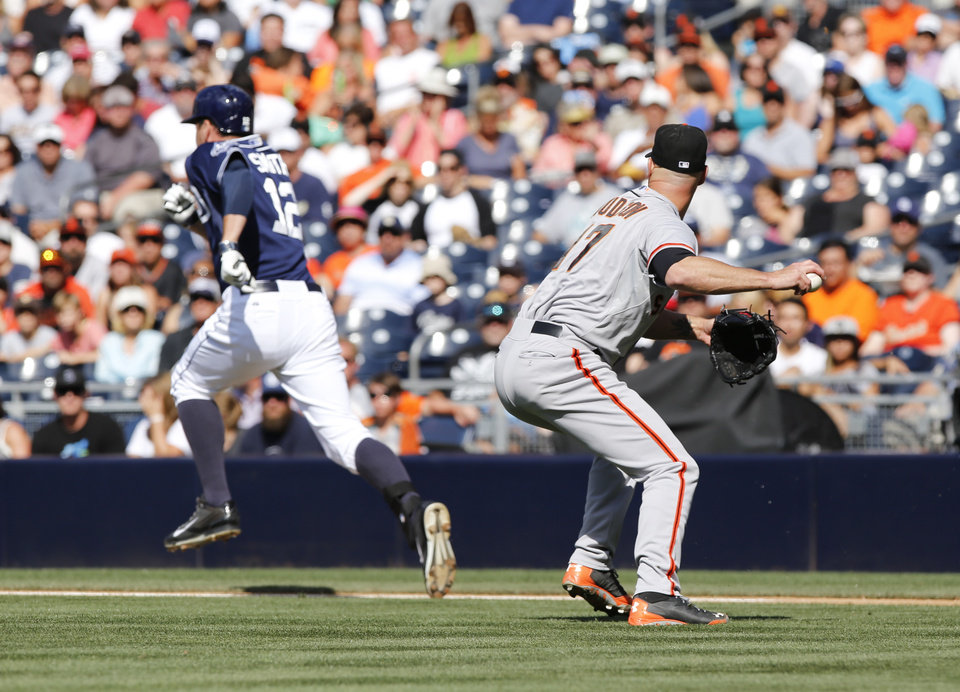 Photo - San Francisco Giants starting pitcher Tim Hudson throws to first to make the out on San Diego Padres' Seth Smith on a grounder during the first  inning of a baseball game Saturday, July 5, 2014, in San Diego. (AP Photo/Don Boomer)