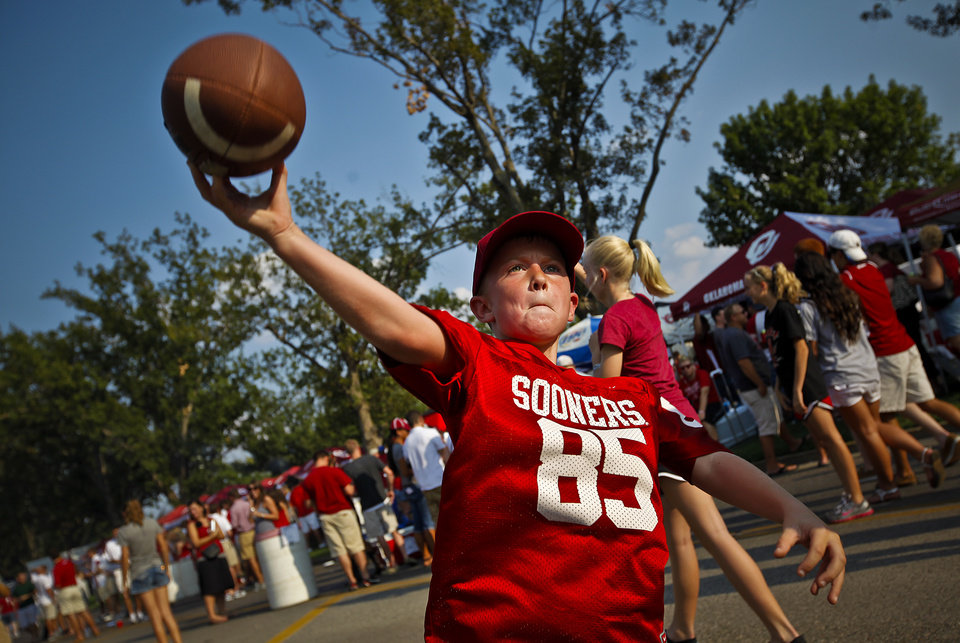 Photo - Logan Gauchat, 9, of Yukon, throws the ball to a friend while tailgating before the college football game between the University of Oklahoma Sooners (OU) and the Tulsa University Hurricanes (TU) at the Gaylord Family-Memorial Stadium on Saturday, Sept. 3, 2011, in Norman, Okla. 