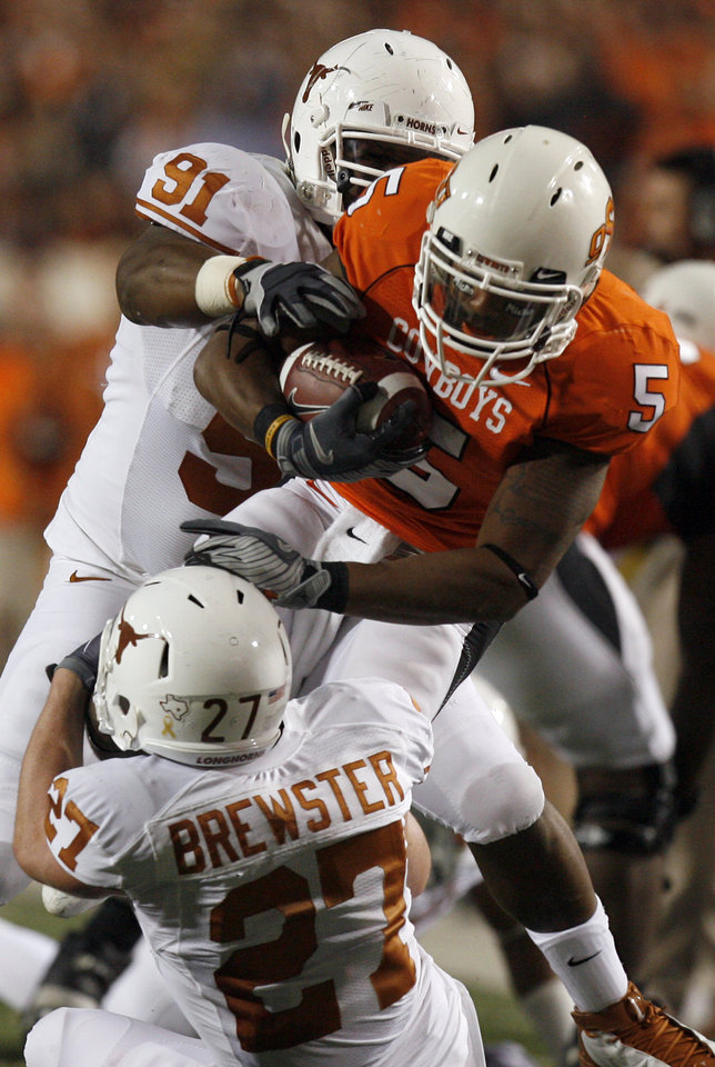 Photo - OSU's Keith Toston (5) is brought down by Texas's Kheeston Randell (91) and Nolan Brewster (27) during the college football game between the Oklahoma State University Cowboys (OSU) and the University of Texas Longhorns (UT) at Boone Pickens Stadium in Stillwater, Okla., Saturday, Oct. 31, 2009. Photo by Sarah Phipps, The Oklahoman