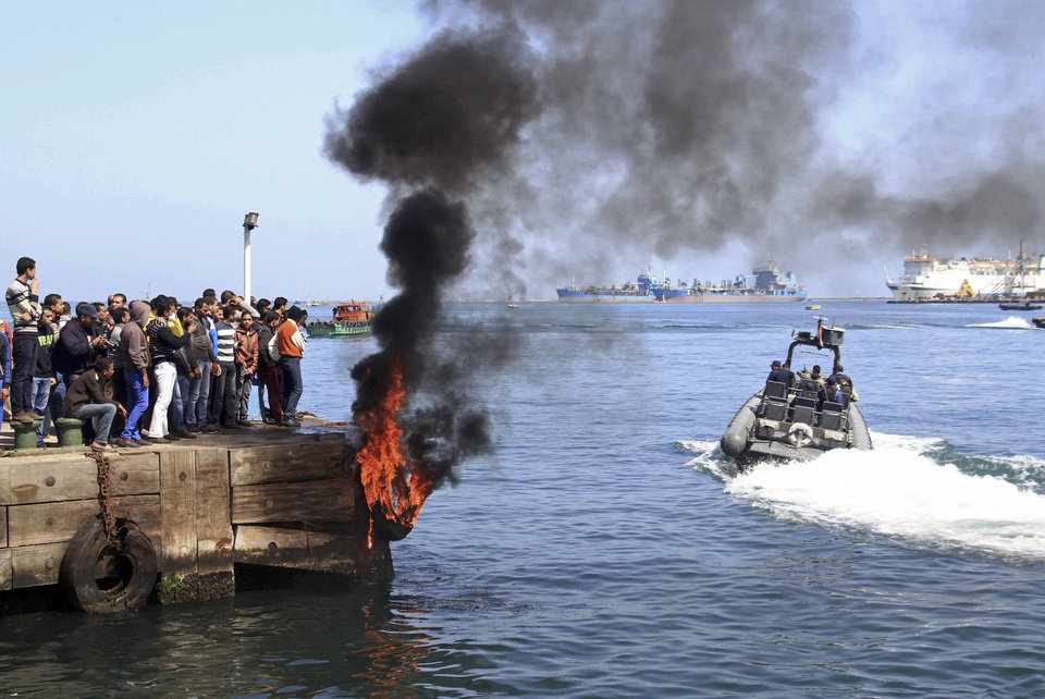 Photo - Several protesters set fire to tires on the city's dock in an attempt to prevent ships from coming in to the strategic city of Port Said at the Mediterranean end of the Suez Canal, in Egypt, Saturday, March 9, 2013. An Egyptian court on Saturday confirmed the death sentences against 21 people for taking part in a deadly 2012 soccer riot but acquitted seven police officials for their alleged role in a trial that has been the source of some of the worst unrest to hit Egypt in recent weeks. (AP Photo/Ahmed Ramadan)