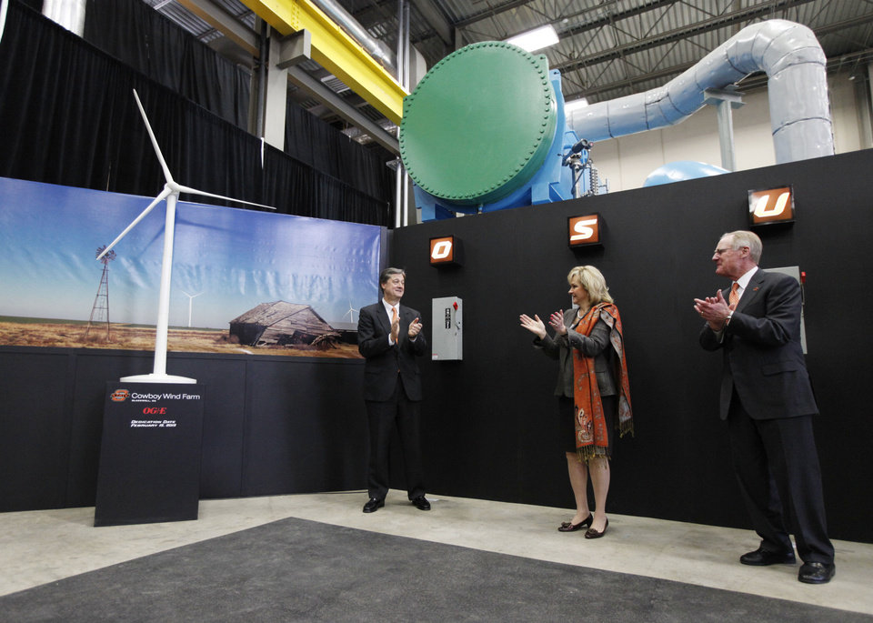 OG&E President Peter Delaney, left, Gov. Mary Fallin, and OSU President Burns Hargis celebrate after flipping symbolic switches to mark the completion of a 60-megawatt wind farm near Blackwell that will help supply power to the OSU campus in Stillwater. PHOTO BY PAUL HELLSTERN, THE OKLAHOMAN <strong>PAUL HELLSTERN</strong>