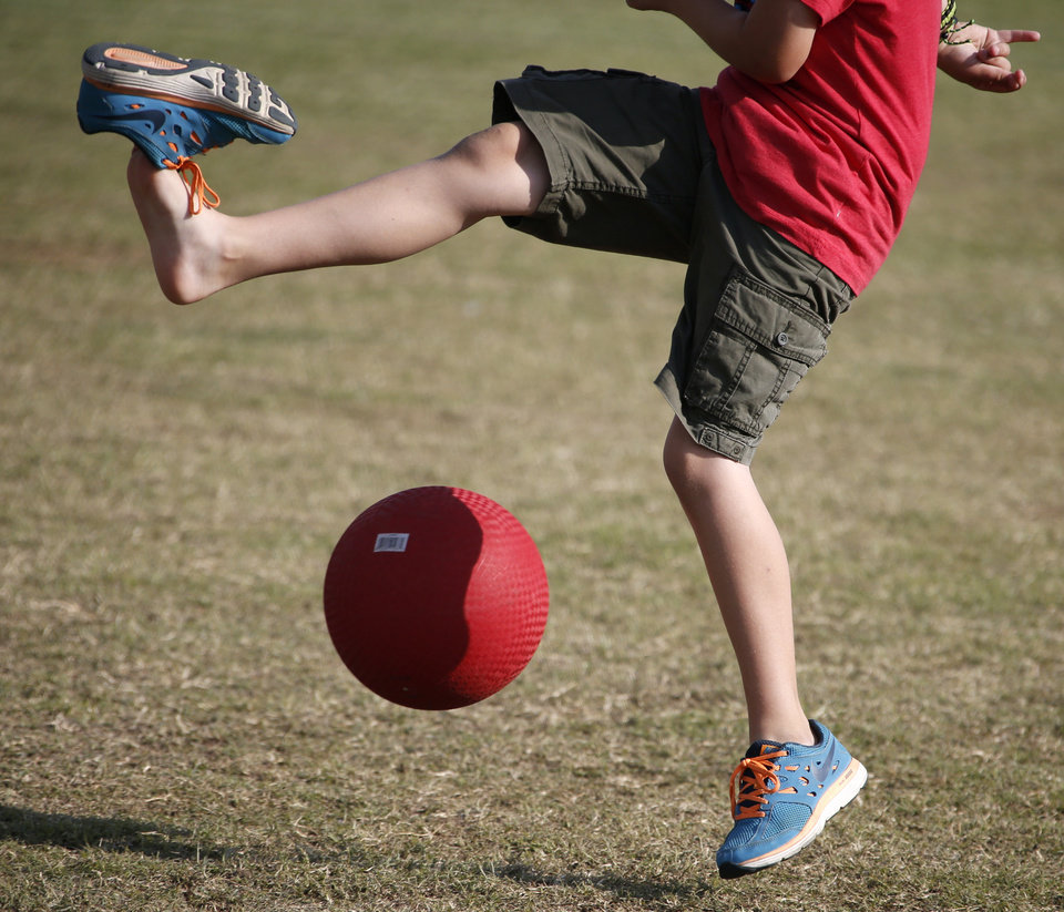 Photo -  James Speegle's son Carson Jantz loses his shoes as he kicks the ball during a kickball game demonstration for the World Adult Kickball League in Oklahoma City on June 10. Photos by Bryan Terry, The Oklahoman   Bryan Terry -  THE OKLAHOMAN