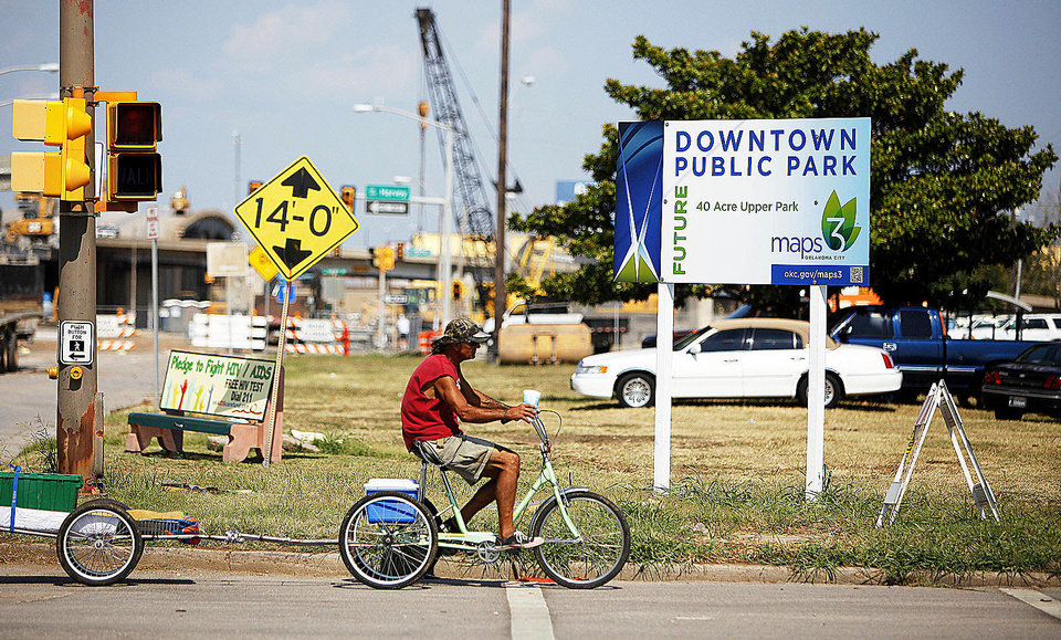 Photo - A man rides past property on the corner of SW 3rd and Hudson on Thursday. The city has filed an eminent domain suit for MAPS park use. Photo by Bryan Terry, The Oklahoman