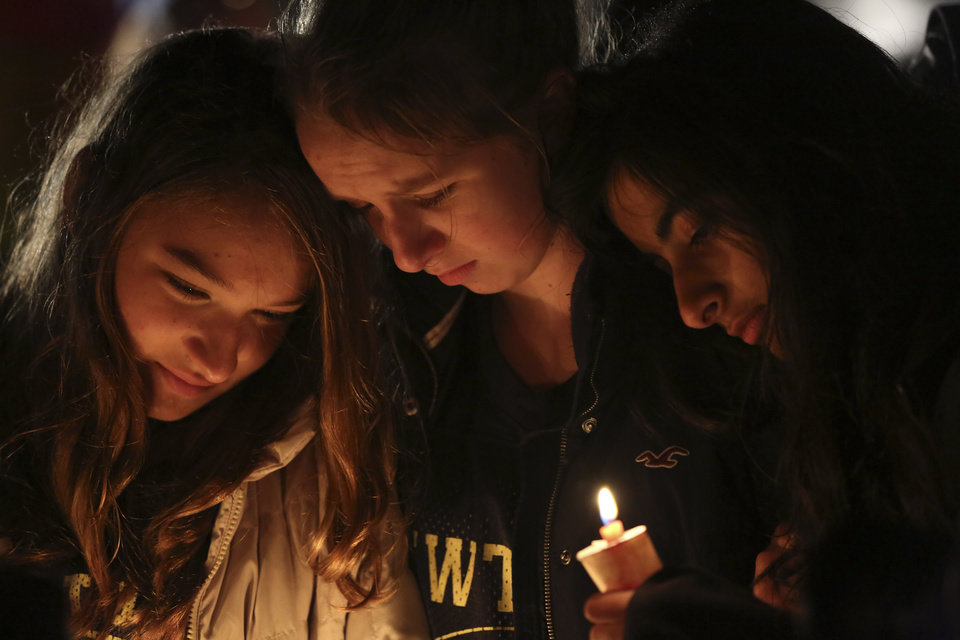 Kate Suba, left, Jaden Albrecht, center, and Simran Chand pay their respects at one of the makeshift memorials in honor of the victims of the Sandy Hook Elementary School shooting, Sunday, Dec. 16, 2012, in Newtown, Conn. A gunman opened fire at the school on Friday, killing 26 people, including 20 children before killing himself on Friday. (AP Photo/Mary Altaffer)
