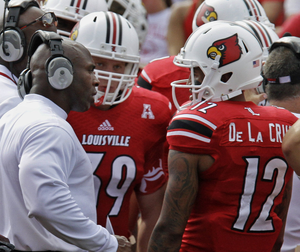 Photo - Louisville coach Charlie Strong, left, talks with wide receiver Kai De La Cruz (12) and fullback Griffin Uhl (39) during a time-out in the second quarter of an NCAA college football game in Louisville, Ky., Sunday, Sept. 1, 2013 against Ohio University. (AP Photo/Garry Jones)