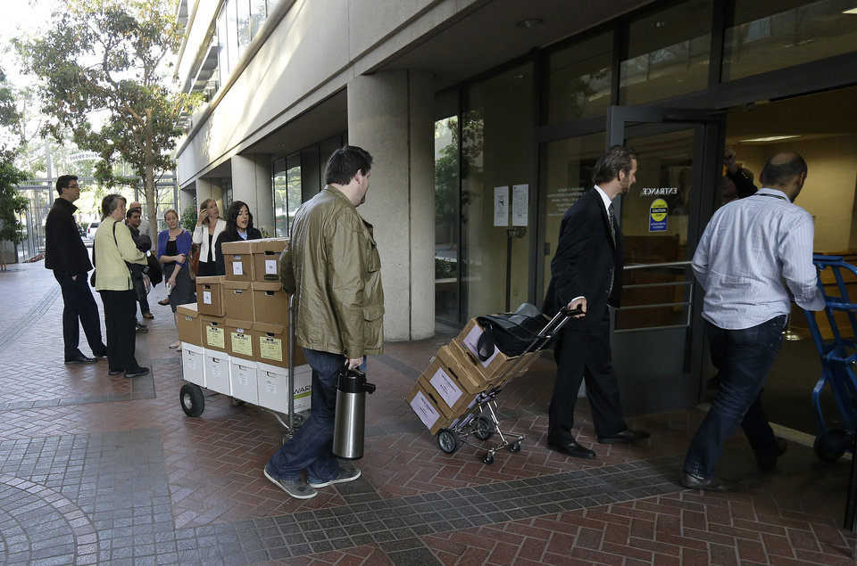 Photo - Boxes containing documents related to the Apple Inc. v. Samsung case are taken into a federal courthouse in San Jose, Calif., Tuesday, April 29, 2014. Lawyers for both companies are expected to deliver closing arguments Tuesday before jurors are sent behind closed doors to determine a verdict in a closely watched trial over the ownership of smartphone technology. (AP Photo/Jeff Chiu)
