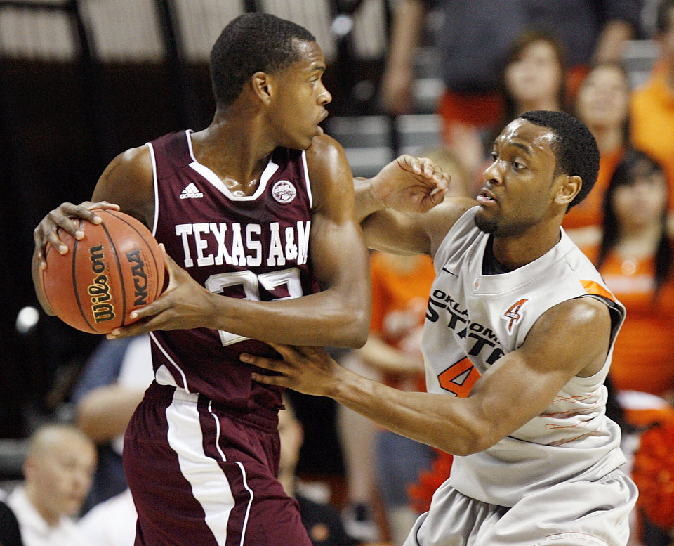 Photo - Texas A&M's Khris Middleton (22) holds the ball as OSU's Brian Williams (4) defends during a men's college basketball game between the Oklahoma State University Cowboys and Texas A&M University Aggies at Gallagher-Iba Arena in Stillwater, Okla., Saturday, Feb. 25, 2012. OSU won, 60-42. Photo by Nate Billings, The Oklahoman