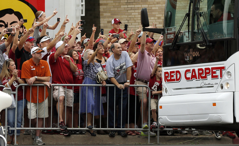Photo - OU and UT fans watch the Sooners' buses arrive before the Red River Rivalry college football game between the University of Oklahoma Sooners and the University of Texas Longhorns at the Cotton Bowl Stadium in Dallas, Saturday, Oct. 12, 2013. Photo by Nate Billings, The Oklahoman