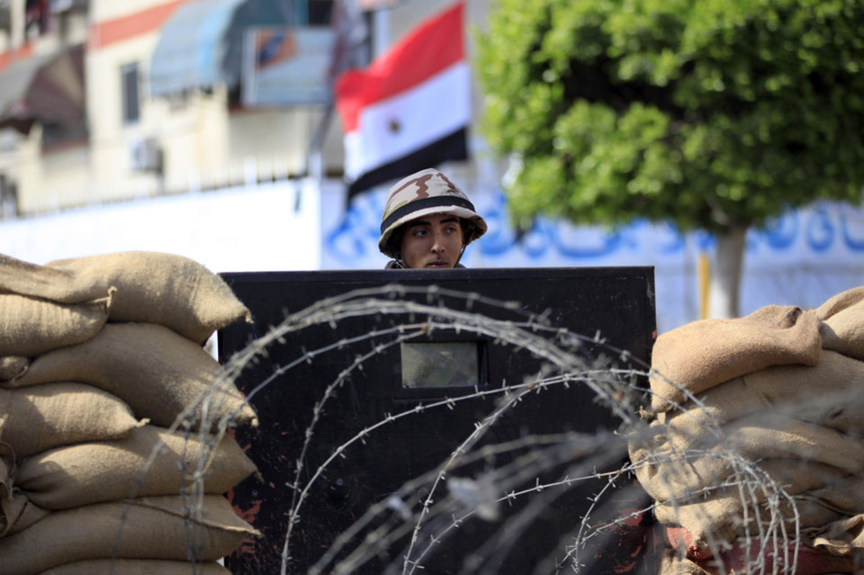 Photo - Egyptian soldiers stand guard outside the prison in Port Said, Egypt, Saturday, March 9, 2013. An Egyptian court on Saturday confirmed death sentences against 21 people for their role in a deadly 2012 soccer riot that killed more than 70 people in the city of Port Said. (AP Photo/Khalil Hamra)