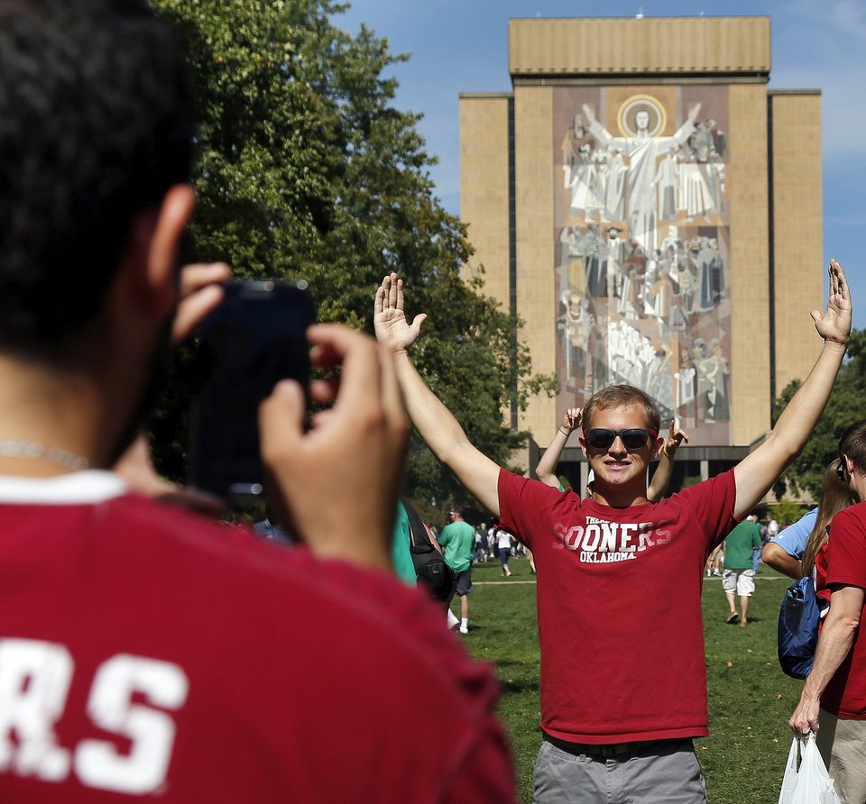 "Photo - OU student Brad Moery, of Edmond, Okla., poses in front of ""The Word of Life"" mural, commonly referred to as Touchdown Jesus, as fellow student Derek Garcia, of Corinth, Texas, takes his picture before a college football game between the University of Oklahoma Sooners (OU) and the Notre Dame Fighting Irish at Notre Dame Stadium in South Bend, Ind., Saturday, Sept. 28, 2013. Photo by Nate Billings, The Oklahoman"