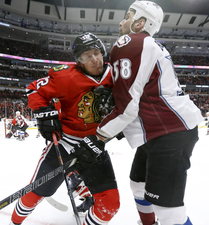 Photo - Chicago Blackhawks center Peter Regin (12) and Colorado Avalanche left wing Patrick Bordeleau collide during the first period of an NHL hockey game Tuesday, March 4, 2014, in Chicago. (AP Photo/Charles Rex Arbogast)