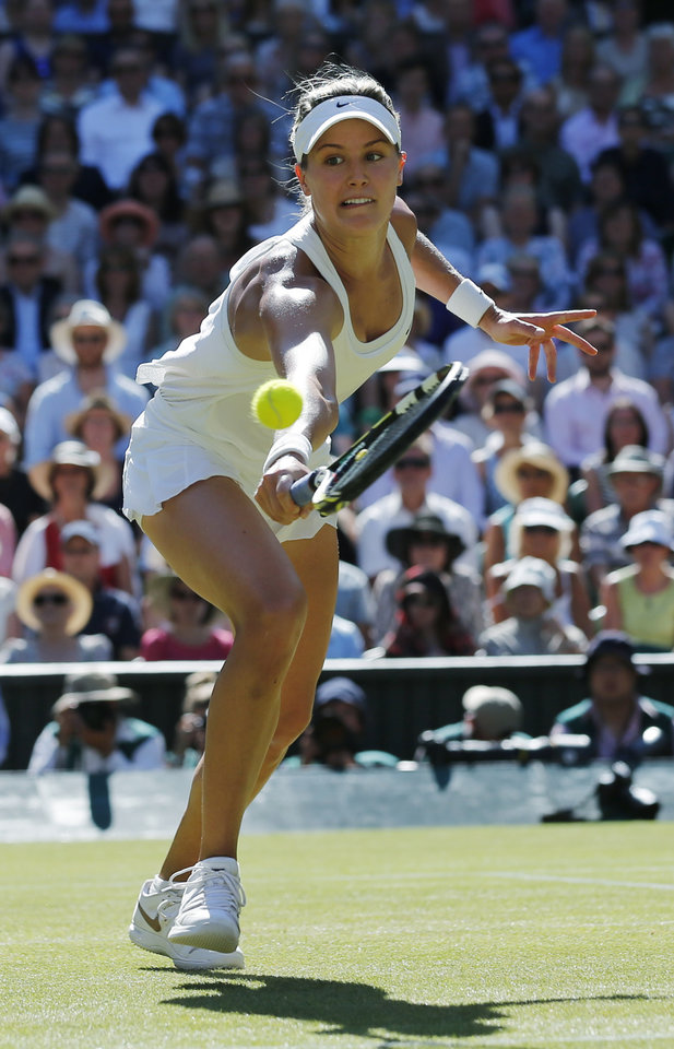 Photo - Eugenie Bouchard of Canada runs to play a return to Simona Halep of Romania during their women's singles semifinal match at the All England Lawn Tennis Championships in Wimbledon, London, Thursday, July 3, 2014. (AP Photo/Ben Curtis)
