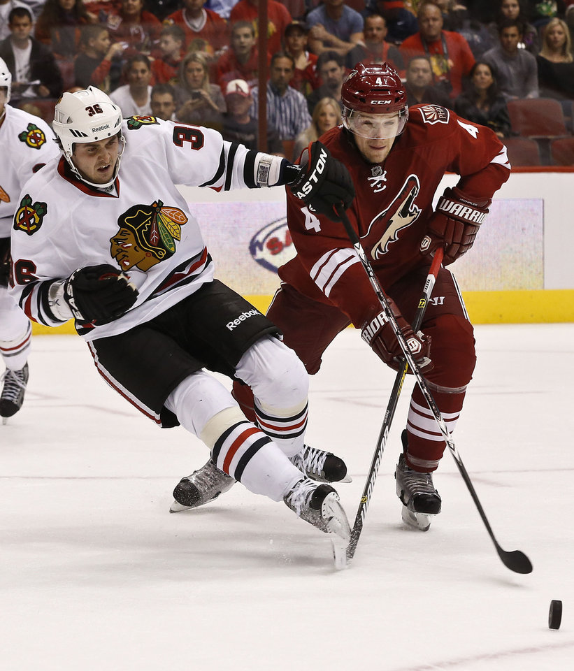 Photo - Phoenix Coyotes' Zbynek Michalek (4), of the Czech Republic, gets called for tripping on Chicago Blackhawks' Dave Bolland (36) during the first period in an NHL hockey game Thursday, Feb. 7, 2013, in Glendale, Ariz.(AP Photo/Ross D. Franklin)